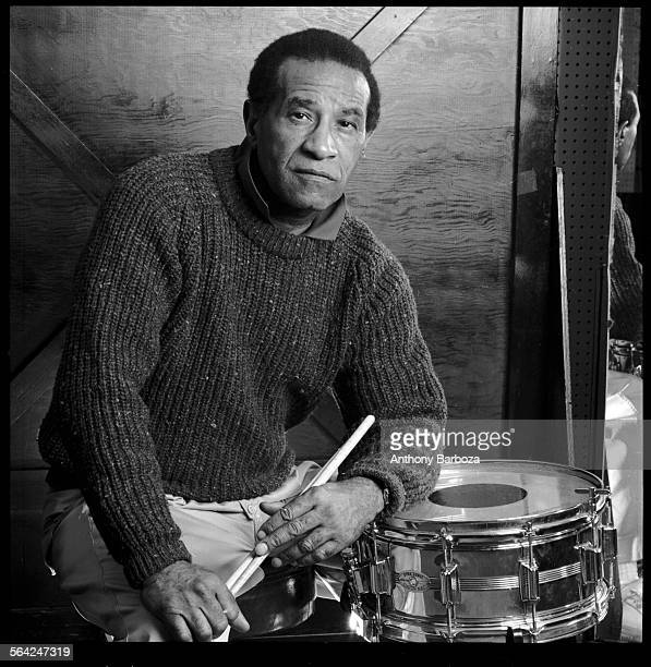 Portrait of American jazz musician Max Roach dressed in a sweater as he poses behind a drum kit with his drumsticks in his hands 1989