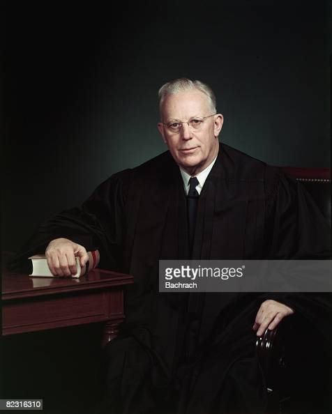 Portrait of American jurist Chief Justice of the Supreme Court Earl Warren as he poses at a table one arm on law book Washington DC 1954