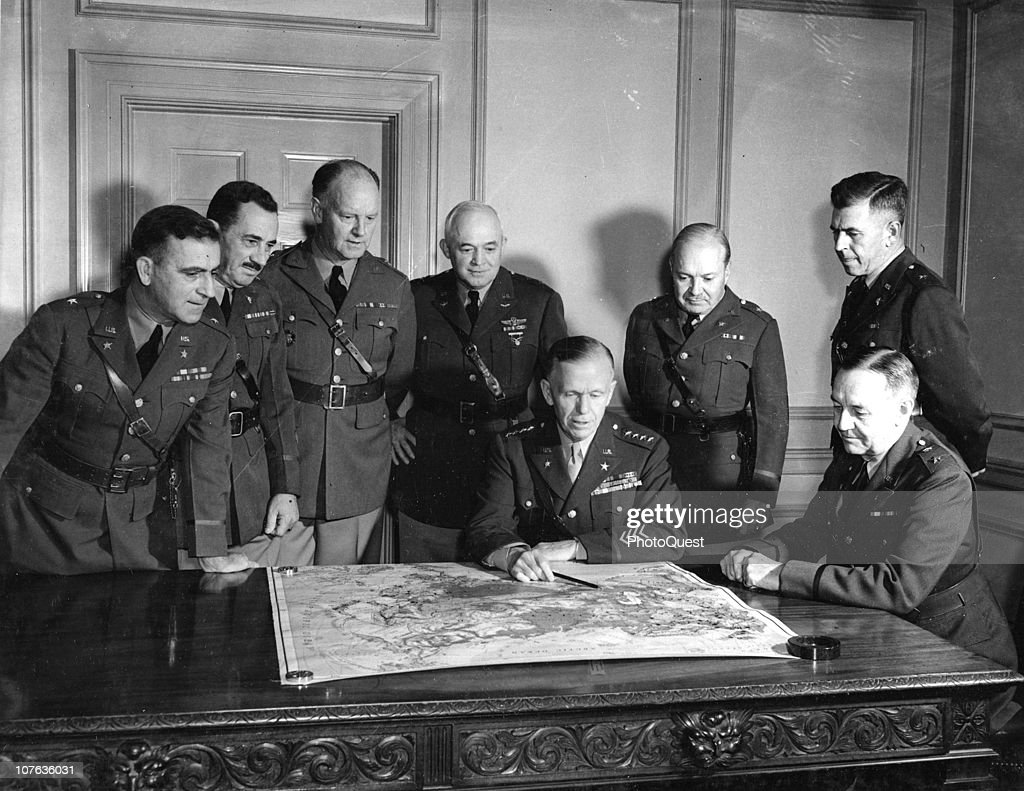 Portrait of American military commander General George C. Marshall (1880 - 1959) (seated, center) as he looks at a map with members of his General Staff in his office at the War Department, Washington DC, November 1941. Pictured are, from left, generals Leonard T. Gerow (1888 - 1972), R.A. Wheeler, Sherman Miles, Henry H. Arnold (1886 - 1950), George C. Marshall, Wade H. Haislip (1889 - 1971), Harry L. Twaddle, and William Bryden.