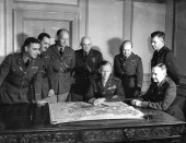 Portrait of American military commander General George C Marshall as he looks at a map with members of his General Staff in his office at the War...