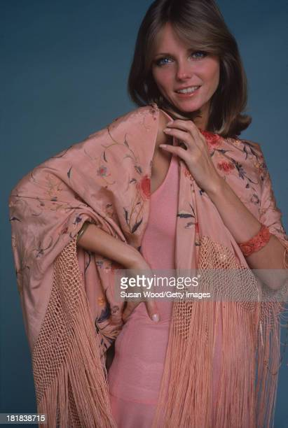 Portrait of American model and actress Cheryl Tiegs as she poses dressed in a rosecolored sleeveless dress and a pink rosepatterned fringed shawl...