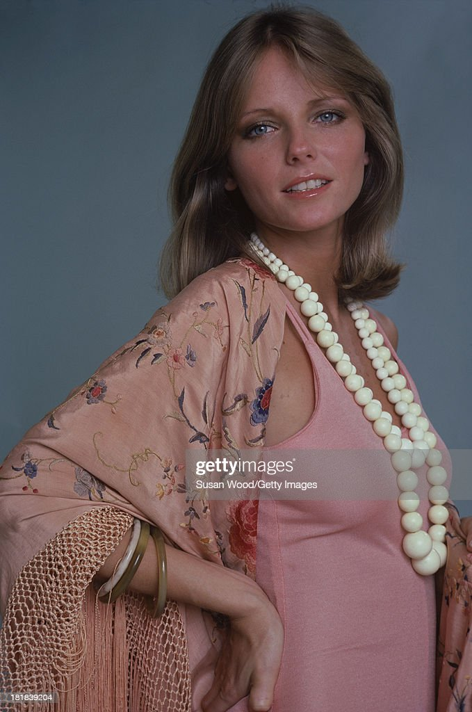 Portrait of American model and actress Cheryl Tiegs as she poses, dressed in a rose-colored, sleeveless dress, a pink, rose-patterned, fringed shawl, and white, beaded necklace, 1974. The photo was taken as part of a cover shoot for the May 1974 issue of Women's Own magazine.