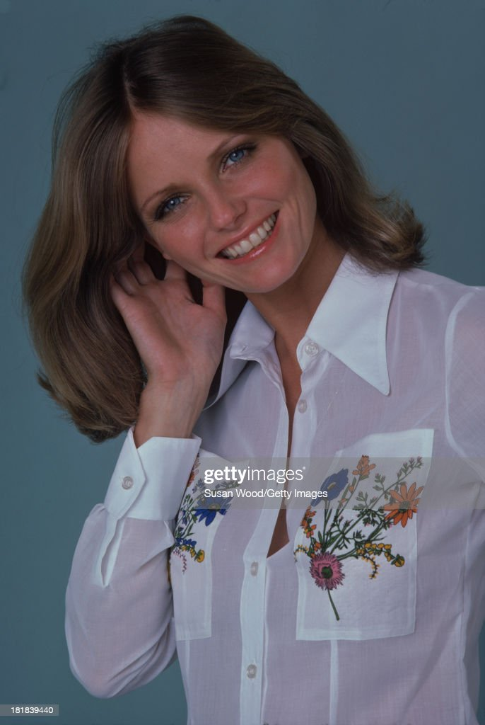 Portrait of American model and actress Cheryl Tiegs as she poses, dressed in a white shirt, with floral embroidery on the pockets, 1974. The photo was taken as part of a cover shoot for the May 1974 issue of Women's Own magazine.
