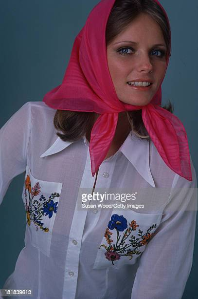 Portrait of American model and actress Cheryl Tiegs as she poses dressed in a white shirt with floral embroidery on the pockets and a pink headscarf...