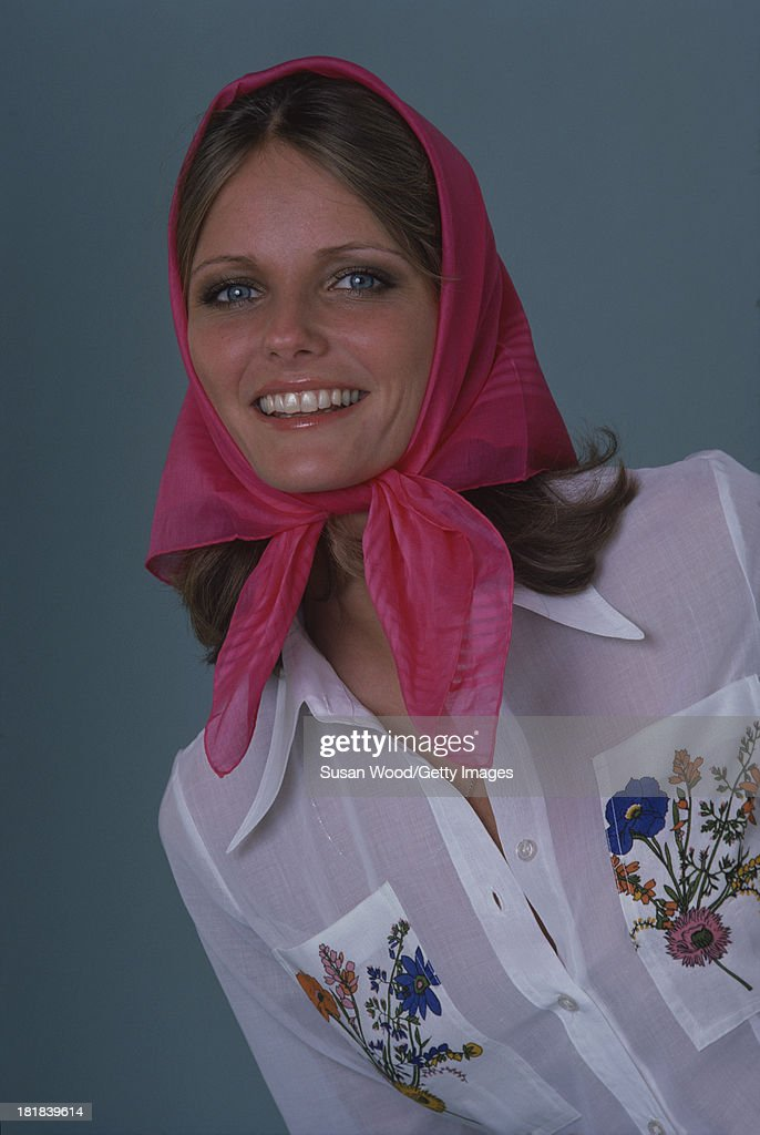 Portrait of American model and actress Cheryl Tiegs as she poses, dressed in a white shirt, with floral embroidery on the pockets, and a pink headscarf, 1974. The photo was taken as part of a cover shoot for the May 1974 issue of Women's Own magazine.