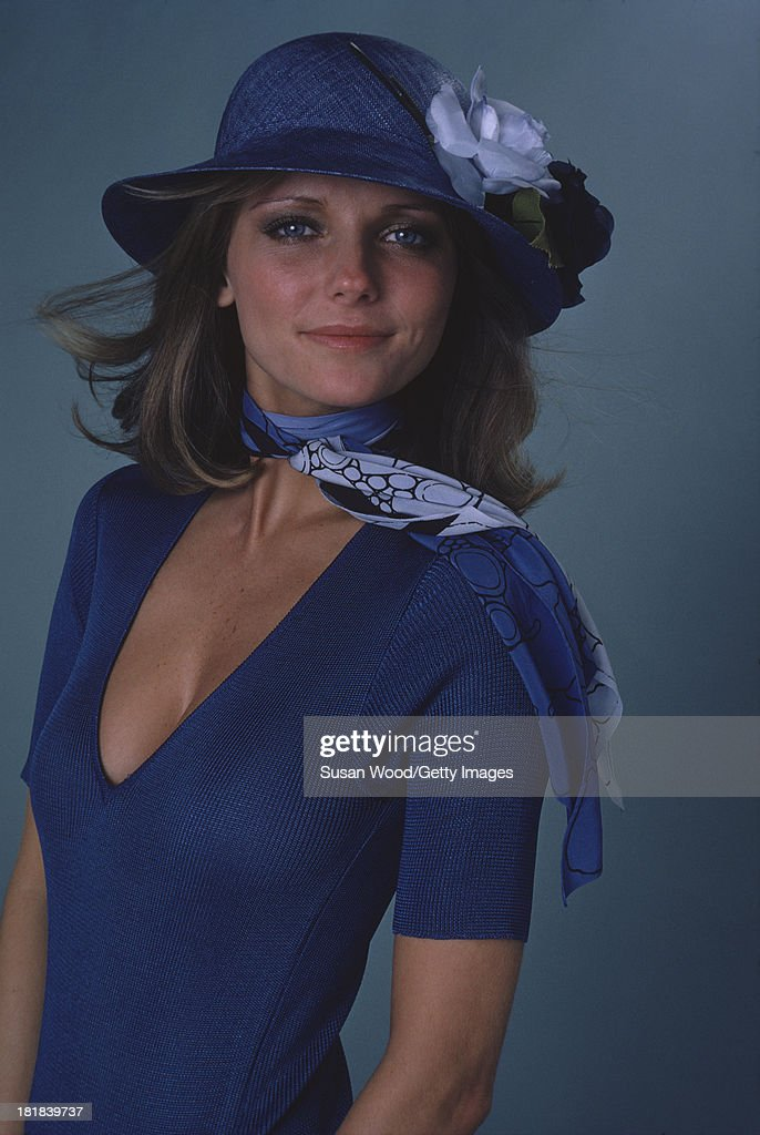 Portrait of American model and actress <a gi-track='captionPersonalityLinkClicked' href=/galleries/search?phrase=Cheryl+Tiegs&family=editorial&specificpeople=211403 ng-click='$event.stopPropagation()'>Cheryl Tiegs</a> as she poses, dressed in a blue print neck scarf, a blue short sleeved V neck sweater, and a blue straw hat, with flower applique, 1974. The photo was taken as part of a cover shoot for the May 1974 issue of Women's Own magazine.