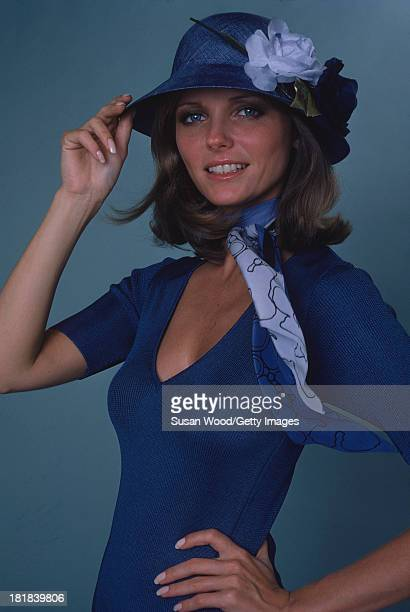 Portrait of American model and actress Cheryl Tiegs as she poses dressed in a blue print neck scarf a blue short sleeved V neck sweater and a blue...