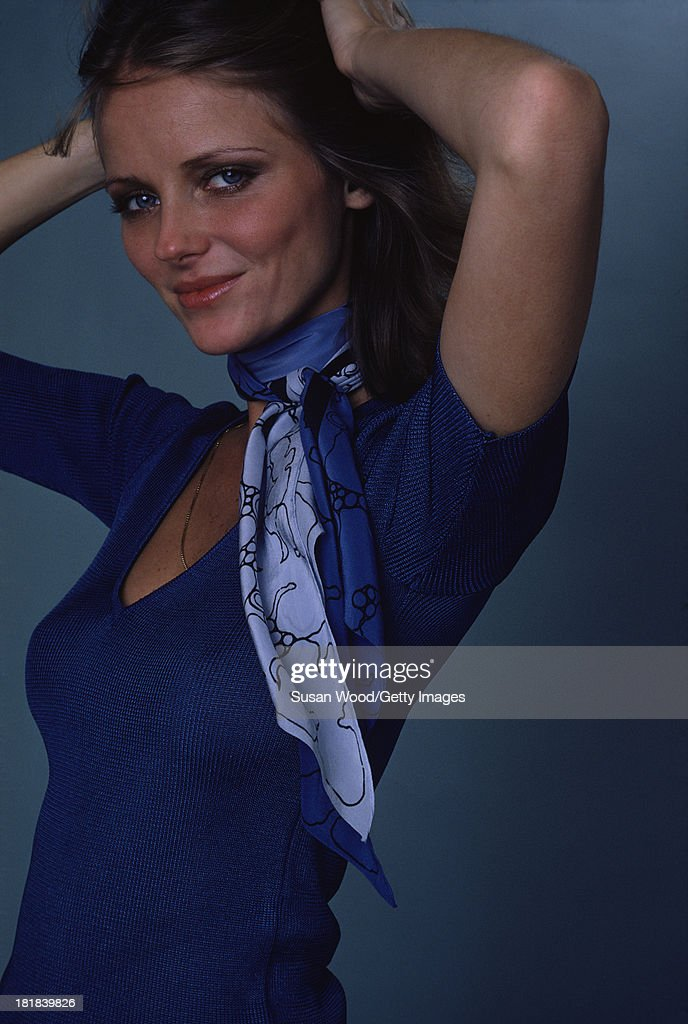 Portrait of American model and actress Cheryl Tiegs as she poses, dressed in a blue-print neck scarf and a blue, short-sleeved, V neck sweater, 1974. The photo was taken as part of a cover shoot for the May 1974 issue of Women's Own magazine.