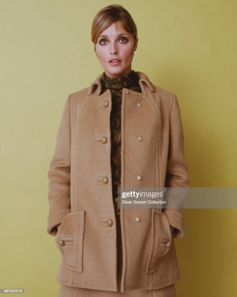Portrait of American model and actress Sharon Tate (1943 - 1969), her hands in her coat-pockets, as she poses against a yellow background, late 1960s.