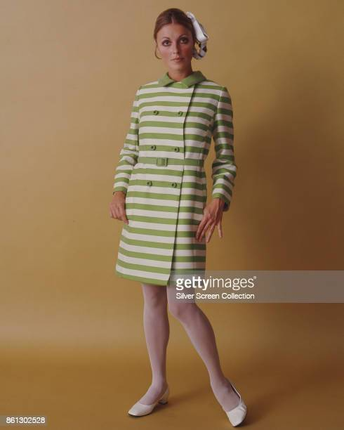Portrait of American model and actress Sharon Tate her thumbs in the pockets her horizontally striped green and white dress as she poses against a...