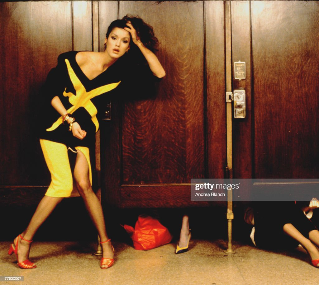 Portrait of American model Janice Dickinson as she stands, knees together, in a black and an yellow outfit, outside a line of occupied stalls in a restroom during aphotoshoot for Italian Vouge, 1983.