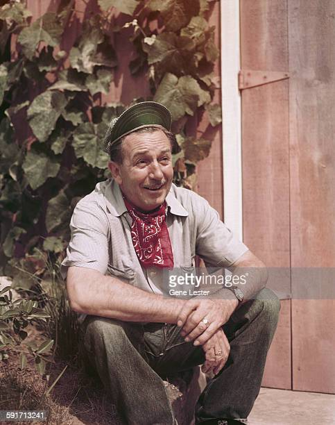 Portrait of American movie producer artist and animator Walt Disney as he sits outdoors beside a wooden door California early to mid 1950s He wears a...