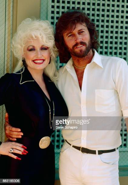 Portrait of American musician actress Dolly Parton and British musician Barry Gibb of the Bee Gees as they pose together at Kenny Rogers' home Los...