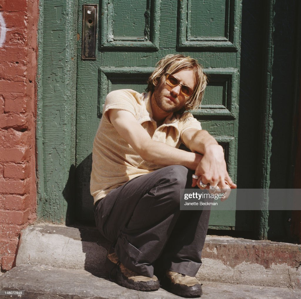 Portrait of American musician Andrew Dorff as he poses in front of a green door, New York, New York, 1998.