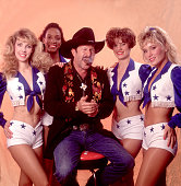 Portrait of American musician author and comedian Kinky Friedman as he poses with four unidentified members of the Dallas Cowboy Cheerleaders...