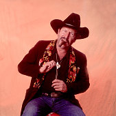 Portrait of American musician author and comedian Kinky Friedman as he poses backstage during the Farm Aid benefit concert at Texas Stadium Dallas...