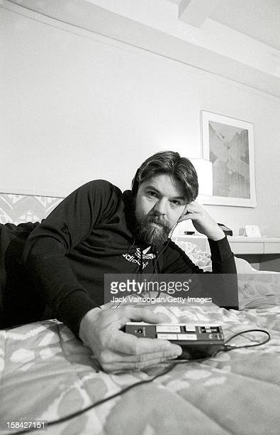 Portrait of American musician Bob Seger as he listen to a portable cassette player on the bed in his hotel room New York New York December 13 1982...