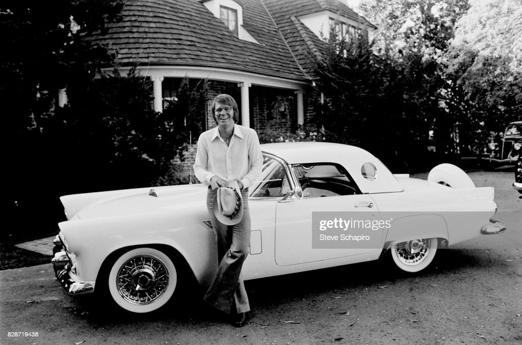 Portrait of American musician Glen Campbell (1936 - 2017) as he smiles and leans against his car, a 1956 Ford Thunderbird, in the driveway of his home, Los Angeles, California, 1978.
