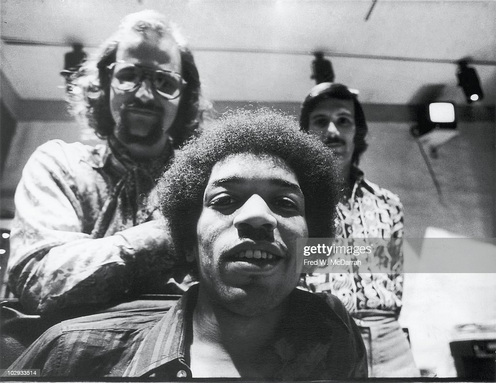 Portrait of American musician <a gi-track='captionPersonalityLinkClicked' href=/galleries/search?phrase=Jimi+Hendrix&family=editorial&specificpeople=234815 ng-click='$event.stopPropagation()'>Jimi Hendrix</a> (1942 - 1970) (seated), South African-born American music producer and engineer <a gi-track='captionPersonalityLinkClicked' href=/galleries/search?phrase=Eddie+Kramer&family=editorial&specificpeople=3270960 ng-click='$event.stopPropagation()'>Eddie Kramer</a> (standing left) and studio manager Jim Marron as they pose in the control room of Hendrix's then still under construction Electric Lady Studio, New York, New York, June 17, 1970.