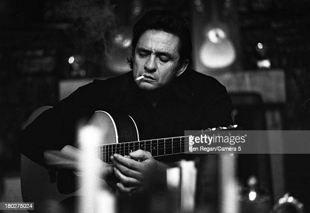 Portrait of American musician Johnny Cash as he plays an acoustic guitar a cigarette in his mouth 1970s