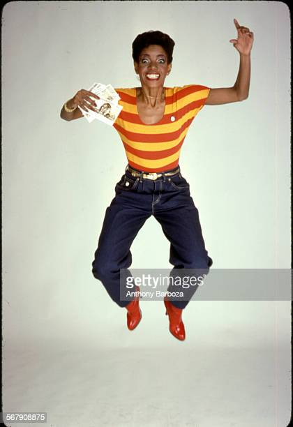 Portrait of American musician Melba Moore dressed in jeans and a red and yellow striped shirt as she jumps into the air New York 1979