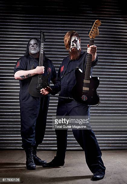 Portrait of American musician Mick Thompson and Jim Root guitarist with heavy metal group Slipknot photographed backstage before a live performance...