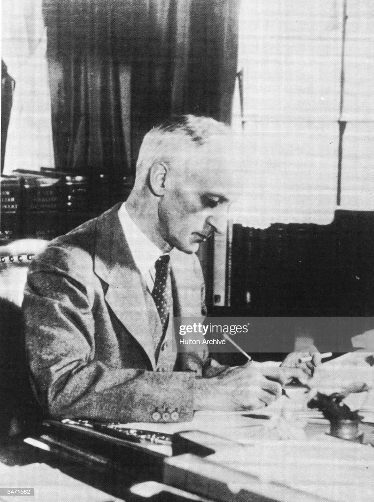 Portrait of American neurosurgeon and Pulitzer Prizewinning author Harvey Cushing as he smokes a cigarette and writes at his desk early 1900s