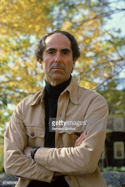Portrait of American novelist Philip Roth dressed in a turtleneck and jacket who stands outdoors with his arms crossed probably 1980s