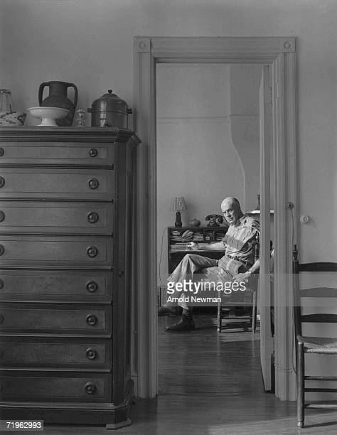 Portrait of American painter Edward Hopper who sits crosslegged at a desk November 1 1941 The photograph is taken from behind an open doorway in...
