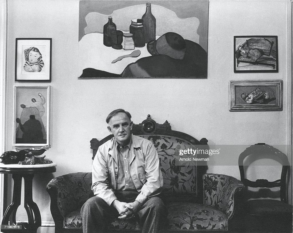 Portrait of American painter Milton Avery (1885 - 1965), who sits on a loveseat with his hands clasped together, April 4, 1944. On the wall hang several paintings, probably the artist's own work.