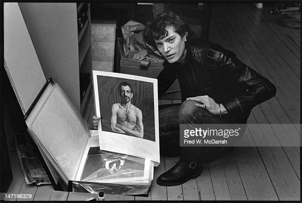 Portrait of American photographer as he poses with a portfolio of his photos in his loft studio New York New York December 22 1979