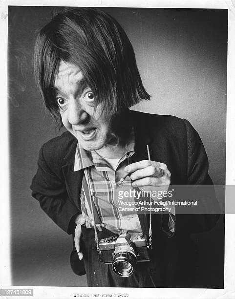 Portrait of American photographer Weegee with a camera around his neck and a wig on his head captioned 'Weegee the Fifth Beatle' 1960s Photo by...