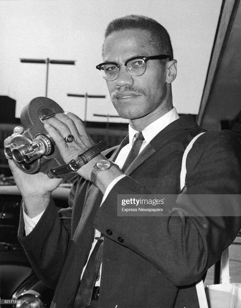Portrait of American political activist and radical civil rights leader <a gi-track='captionPersonalityLinkClicked' href=/galleries/search?phrase=Malcolm+X&family=editorial&specificpeople=70045 ng-click='$event.stopPropagation()'>Malcolm X</a> (1925 - 1965) as he holds an 8mm movie camera in London Airport, London, England, July 9, 1964. Shortly after breaking his affiliation with the Nation of Islam, and just days after his formation of the Organization of Afro-American Unity (OAAU), <a gi-track='captionPersonalityLinkClicked' href=/galleries/search?phrase=Malcolm+X&family=editorial&specificpeople=70045 ng-click='$event.stopPropagation()'>Malcolm X</a> was in London en route to Egypt to attend a meeting of the Organization of African Unity and to meet with the leaders of various African states.