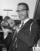 Portrait of American political activist and radical civil rights leader Malcolm X as he holds an 8mm movie camera in London Airport London England...