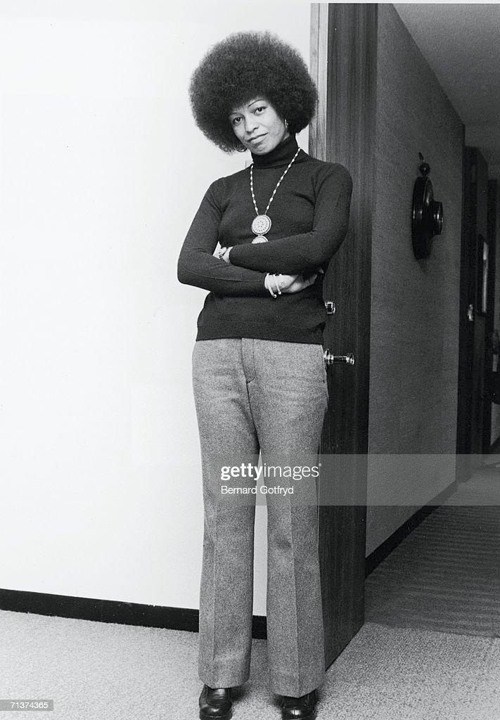 Portrait of American political activist and scholar Angela Davies as she leans against an open door, her arms crossed in front of her, New York, New York, 1974.