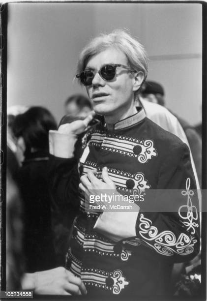 Portrait of American pop artist Andy Warhol as he tries on a marching band uniform in a used clothing store New York New York December 9 1966