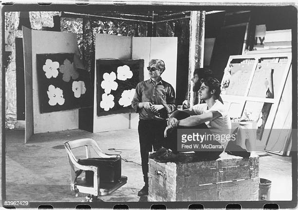 Portrait of American pop artist Andy Warhol future film historian P Adams Sitney and poet Gerard Malanga in the Factory Warhol's studio New York New...