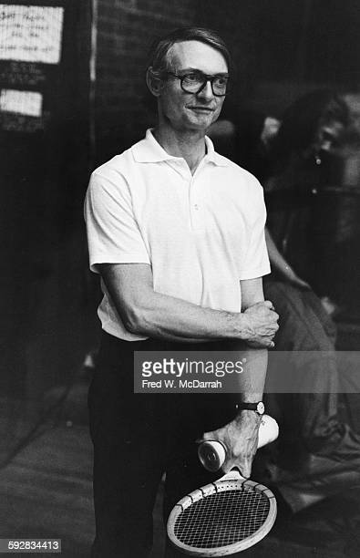Portrait of American Pop artist Roy Lichtenstein as he holds a tennis racket and a can of balls at the Harlem Armory New York New York February 2 1975