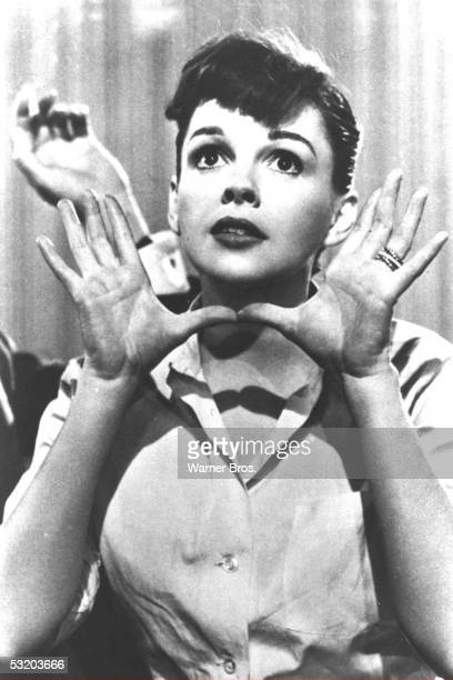 Portrait of American poular singer and actress Judy Garland as she makes the gesture later called 'Jazz Hands' in a still from the film 'A Star is...