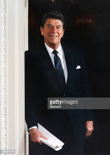 Portrait of American President Ronald Reagan as he leans in a doorway at the White House Washington DC 1983