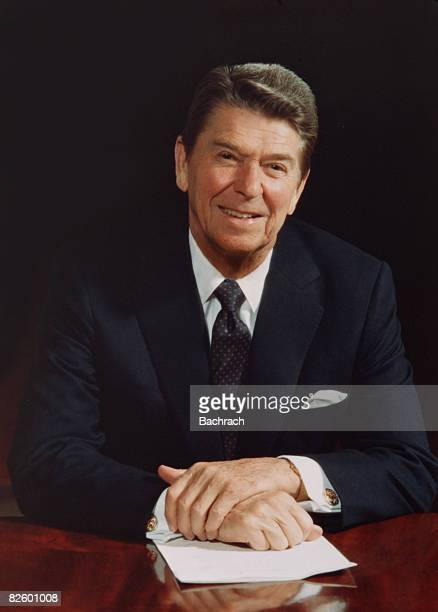 Portrait of American President Ronald Reagan as he sits at a table in the White House and smiles Washington DC 1983