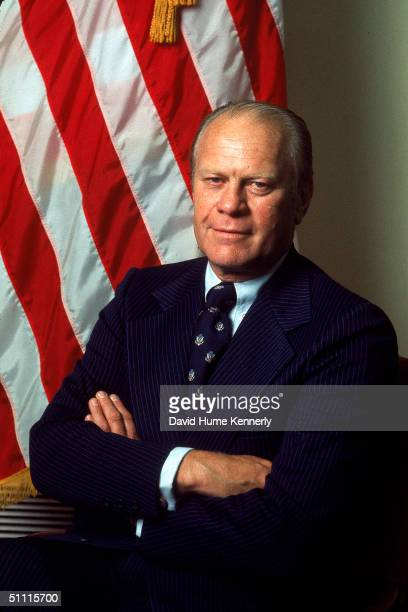 Portrait of American Presisdent Gerald Ford dressed in a blue pinstriped suit as he stands with his arms crossed taken during his first month in...