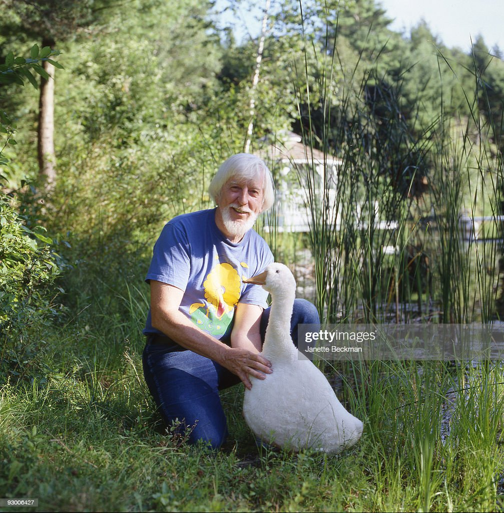 Portrait of American puppeteer Caroll Spinney, best known for his portrayal of Big Bird on 'Sesame Street,' as he poses on a water bank with a plush goose toy, late 1990s or early 2000s.