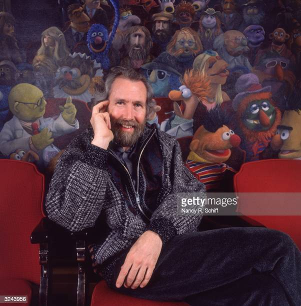 Portrait of American puppeteer Jim Henson sitting in a theater chair in front of a painting of his creation The Muppets