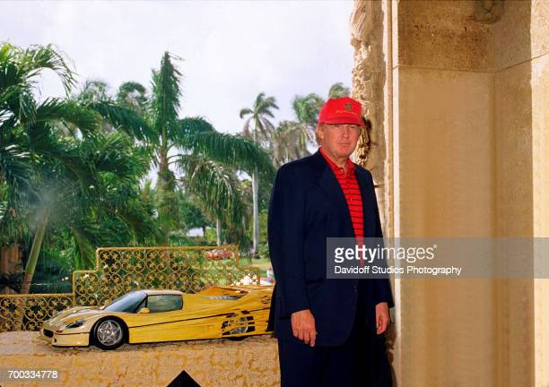 Portrait of American real estate developer Donald Trump as he poses in front of a model of a car at the MaraLago club Palm Beach Florida January 23...