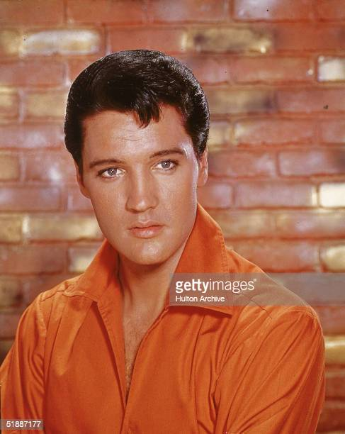 Portrait of American rock and roll singer Elvis Presley dressed in an orange openneck shirt and in front of a brick wall mid 1960s