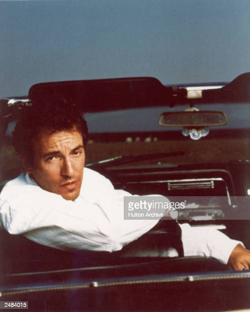 Portrait of American rock singer and songwriter Bruce Springsteen sitting in the driver's seat of a Cadillac convertible circa 1987