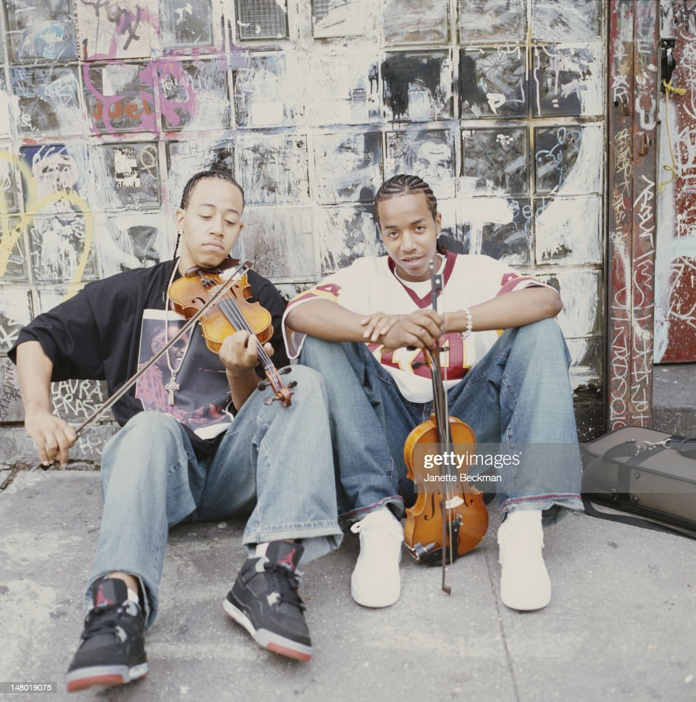 Portrait of American sibling violinists Damien and Tourie Escobar, who perform together as Nuttin' But Stringz, as they sit on a sidewalk and lean against a grafitti-covered wall, New York, New York, 2009.