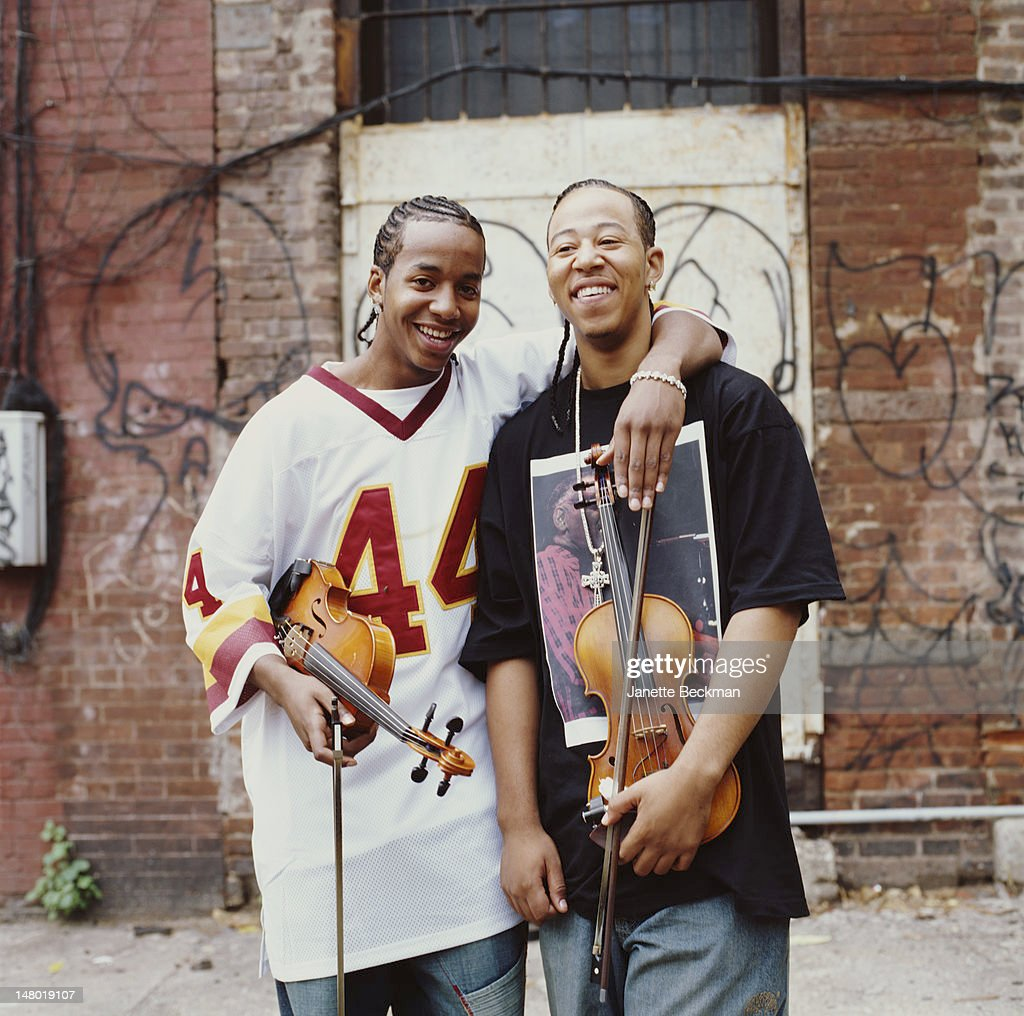 Portrait of American sibling violinists Damien and Tourie Escobar, who perform together as Nuttin' But Stringz, as they pose together in front of a grafitti-covered wall, New York, New York, 2009.