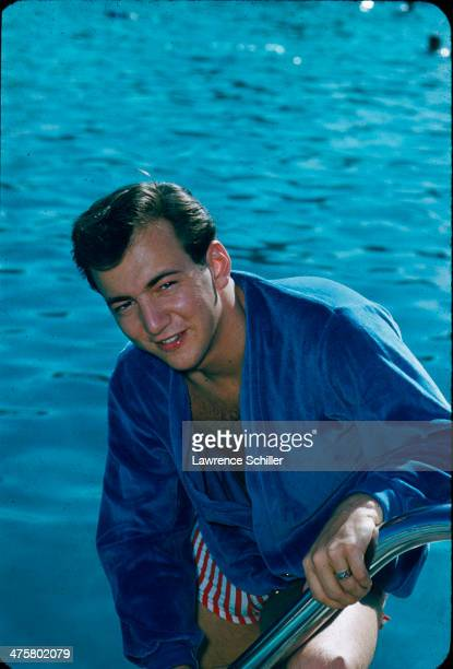 Portrait of American singer and actor Bobby Darin as he poses in a shirt and swim trunks on the steps of a swimming pool Las Vegas Nevada 1959